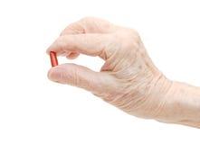 Ältere Hand mit den Tabletten getrennt auf Weiß Stockbild