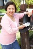 Ältere hispanische Frau, die Briefkasten überprüft Stockbild