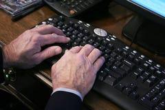 Ältere Hände auf Tastatur Stockfoto