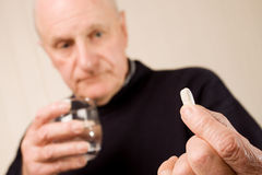 Ältere Holdingtablette oder -pille des älteren Mannes mit Wasser Lizenzfreie Stockfotos