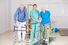 Ältere Leute, die gehende Übung in der Physiotherapie tun Lizenzfreies Stockfoto