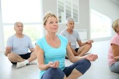 Ältere Leute, welche die entspannende Meditation tun Stockfotos