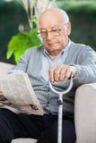 Ältere Mann-Lesezeitung am Pflegeheim Stockfoto