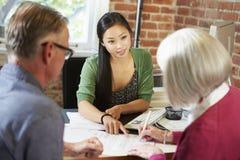 Ältere Paar-Sitzung mit Finanzberater im Büro Stockfotos