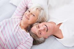 Ältere Paare, die auf Bett liegen Lizenzfreie Stockfotos