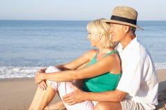 Ältere Paare, die auf dem entspannenden Strand sitzen Lizenzfreie Stockfotos