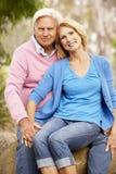 Ältere Paare, die auf Wand sitzen Stockbilder