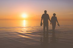 Ältere Paare, die bei Sonnenuntergang gehen Lizenzfreies Stockfoto
