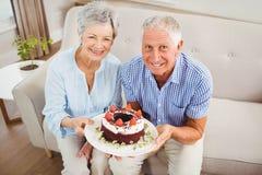 Ältere Paare, die einen Kuchen halten Stockbild