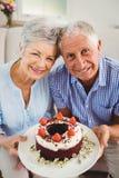 Ältere Paare, die einen Kuchen halten Stockfotografie