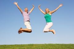 Ältere Paare, die in einer Luft springen Stockfotos