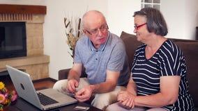 ?ltere Paare, die online unter Verwendung der Kreditkarte auf Laptop kaufen stock video