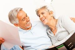 Ältere Paare, die Schreibarbeit tun Stockbild