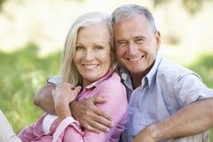 Ältere Paare, die in Sunny Summer Field sich entspannen Stockfotos