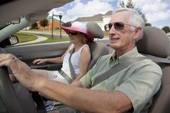 Ältere Paare, die umwandelbares Auto antreiben Stockfotos