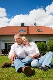 Ältere Paare, die vor ihrem Haus sitzen Stockfotos