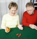 Ältere Paare, die Würfel spielen Stockbild