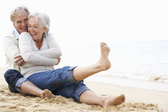 Ältere Paare, die zusammen auf Strand sitzen Stockfotos