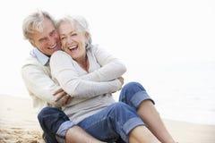 Ältere Paare, die zusammen auf Strand sitzen Lizenzfreie Stockfotos