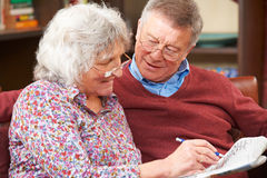 Ältere Paare, die zusammen Kreuzworträtsel in der Zeitung tun Lizenzfreies Stockbild