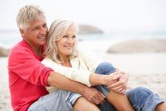 Ältere Paare am Feiertag, der auf Winter-Strand sitzt Stockfotografie
