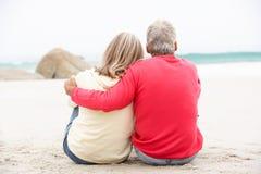 Ältere Paare am Feiertag, der auf Winter-Strand sitzt Stockbild