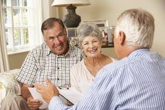 Ältere Paare im Ruhestand, die auf Sofa Talking To Financial Advisor sitzen Lizenzfreie Stockbilder