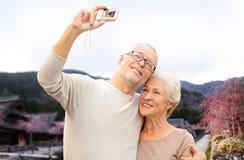 Ältere Paare mit Kamera über asiatischem Dorf Lizenzfreie Stockfotos
