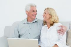 Ältere Paare mit Laptop auf Sofa in einem Haus Lizenzfreie Stockfotos