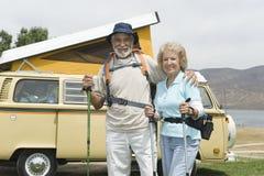 Ältere Paare mit Wanderstöcken und Campervan Stockfoto
