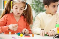 Ältere Schwester mit dem jüngeren Bruder gemacht mit Tonfiguren, playin Lizenzfreies Stockbild