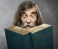 Älterer alter Mann las Buch, erstaunliches Gesichts-verrückte entsetzte Augen Stockfoto