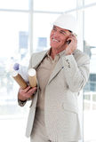 Älterer Architekt auf tragenden Lichtpausen des Telefons Lizenzfreie Stockfotos