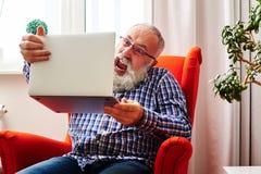 Älterer auf dem Stuhl sitzender und schreiender Mann Lizenzfreies Stockbild