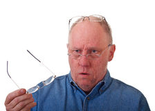 Älterer Balding Mann verwirrt über Lesegläsern Stockfoto