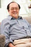 Älterer chinesischer Mann, der sich zu Hause auf Sofa entspannt Lizenzfreie Stockfotografie