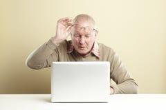Älterer, der Laptop verwendet Lizenzfreie Stockbilder