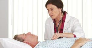 Älterer Doktor, der auf das Herz des reifen Patienten hört Stockfotografie