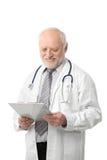 Älterer Doktor, der das Papierlächeln betrachtet Stockfoto