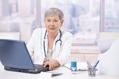 Älterer Doktor, der Laptop-Computer verwendet Stockfoto