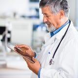 Älterer Doktor, der seinen Tablettecomputer verwendet Stockbild
