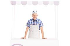 Älterer Eiscremeverkäufer, der hinter einem Eisstand steht Stockfotos