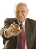 Älterer Geschäftsmann, der ein goldenes Ei anbietet Stockbild