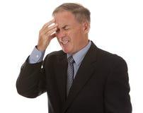 Älterer Geschäftsmann, der Kopfschmerzen hat Stockbild