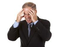 Älterer Geschäftsmann, der Kopfschmerzen hat Lizenzfreies Stockfoto