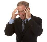 Älterer Geschäftsmann, der Kopfschmerzen hat Stockbilder