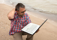 Älterer Geschäftsmann, der mit Notizbuch auf Strand sitzt Lizenzfreie Stockbilder