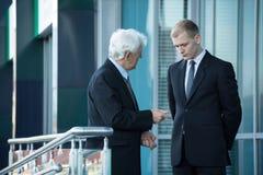 Älterer Geschäftsmann, der mit seinem Angestellten spricht Lizenzfreies Stockbild