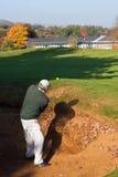 Älterer Golfspieler, der aus einem Bunker im Herbst heraus spielt Stockfoto