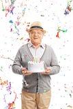 Älterer Herr, der einen Geburtstagskuchen trägt Lizenzfreie Stockfotografie